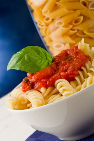 photo of delicious pasta with tomato sauce on blue background