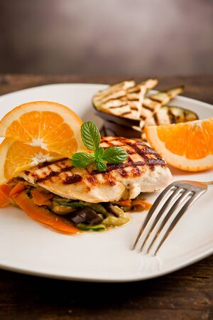 delicious grilled chicken breast with orange on ratatouille bed