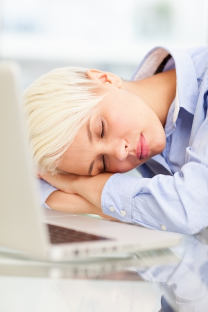 photo of exhausted businesswoman who sleeps on notebook