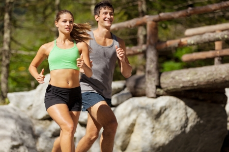 Photo of young sporty couple doing running in the mountains