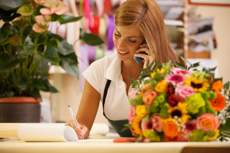 Photo for Florist at the phone with customers for aranging orders - Royalty Free Image