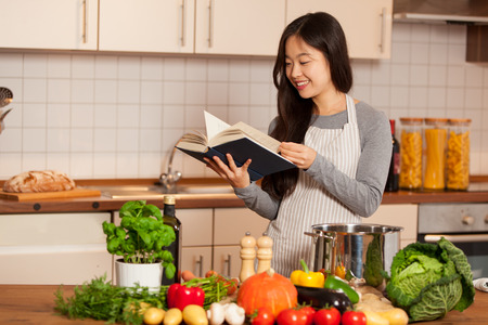 Asian smiling woman looking a cookbook while standing in her kitchen