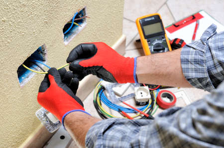Photo pour Electrician technician at work prepares the cable with hands protected by gloves in a residential electrical installation - image libre de droit