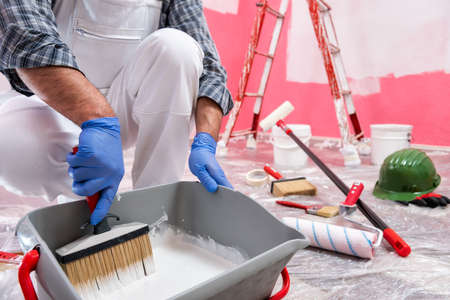 Photo pour Caucasian house painter worker in white overalls, prepare the white paint to paint the pink wall. Construction industry. Work safety. - image libre de droit