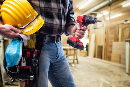 Photo for Carpenter in the carpentry workshop, holding a helmet, goggles, leather gloves, surgical mask to prevent infection by the coronavirus and cordless drill. Covid-19 Pandemic Prevention. - Royalty Free Image