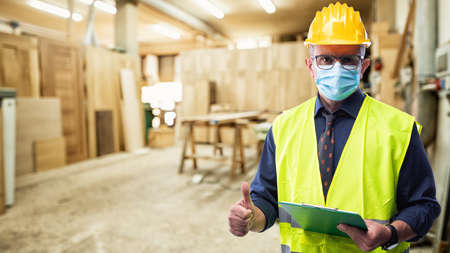Photo for Engineer in carpentry workshop wears surgical mask to prevent Coronavirus spread, makes OK sign with thumb up. Preventing Pandemic Covid-19 at the workplace. - Royalty Free Image