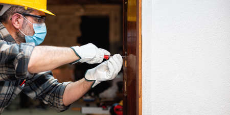 Photo pour Carpenter worker at work repairs and installs a room door, wear the surgical mask to prevent Coronavirus infection. Preventing Pandemic Covid-19 at the workplace. Carpentry. Text space. - image libre de droit