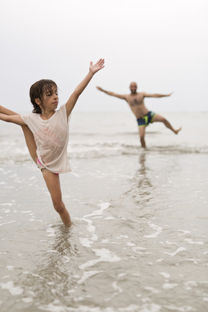 Little girl on a beach doing water gymnastics.
