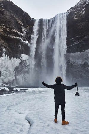 person with a camera in front of snowy waterfall