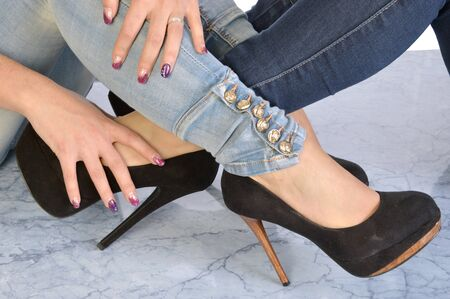 Image of two women symbolically intertwined, in jeans and heeled shoes