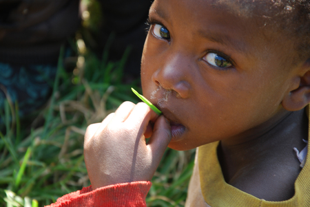 August 8, 2014, Mountain of Kilolo, Kilolo, Tanzania, Africa-The look of an unidentified African child while sucking a blade of grass on the mountain of Kilolo, a look that tells of suffering, misery, poverty and hunger