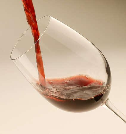 Rotwein fliesst in ein Glas