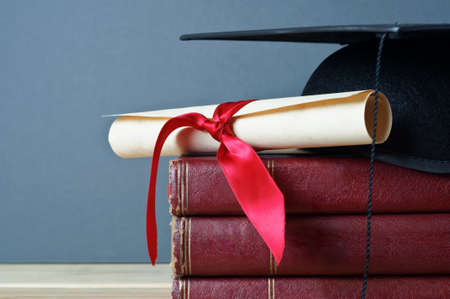 Close up of a mortarboard and graduation scroll on top of a pile of old, worn books, placed on a light wood table with a grey background.