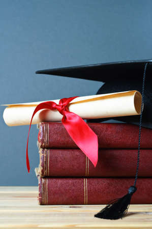 A stack of old, worn books with a mortarboard and ribbon tied scroll on top, placed on a wooden table with a grey background.