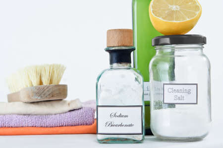 A range of non-toxic cleaning products in glass jars and bottles with a stack of cleaning cloths and scrubbing brush.  Copy space upper left.