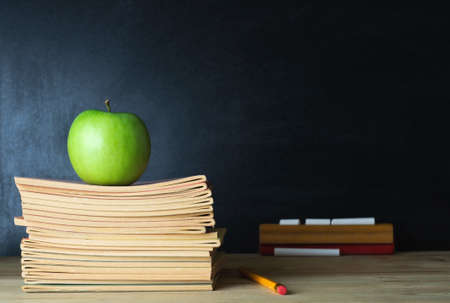 Photo pour A school teacher's desk with stack of exercise books and apple in left frame. A blank blackboard in soft focus background provides copy space. - image libre de droit