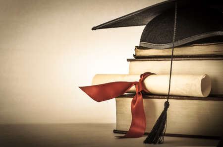 Photo pour A mortarboard and graduation scroll, tied with red ribbon, on a stack of old battered book with empty space to the left.  Slightly undersaturated with vignette for vintage effect. - image libre de droit