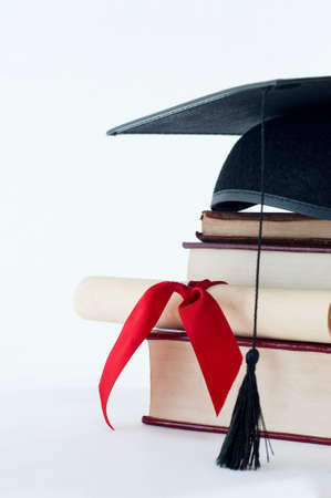 A graduation mortarboard on top of a stack of books, with parchment scroll tied in red ribvon.