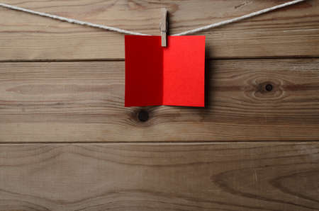 A blank, red greetings or Christmas card, pegged to string against old wood planked background.  Copy space on card and below.