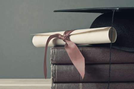 Photo pour Close up of a mortarboard and graduation scroll on top of a pile of old, worn books, placed on a light wood table with a grey background.  Faded, washed out colours for vintage or retro appearance. - image libre de droit