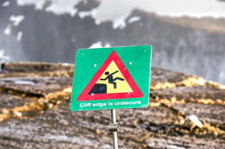 Warning sign at the edge of a ravine in Iceland,  supported by a graphic illustration, indicating the cliff edge is unsafe