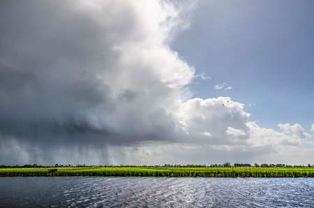 Photo pour Rain shower dropping its loads over the Alblasserwaard polder in the Netherlands followed by a bright interval - image libre de droit