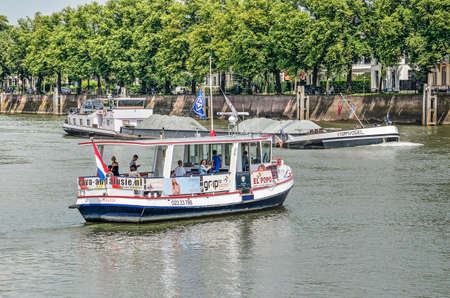Photo for Deventer, The Netherlands, June 18, 2019: small pdestrian ferry has to wait a few moments for an inland barge to pass on the river IJssel before making the crossing to the city - Royalty Free Image