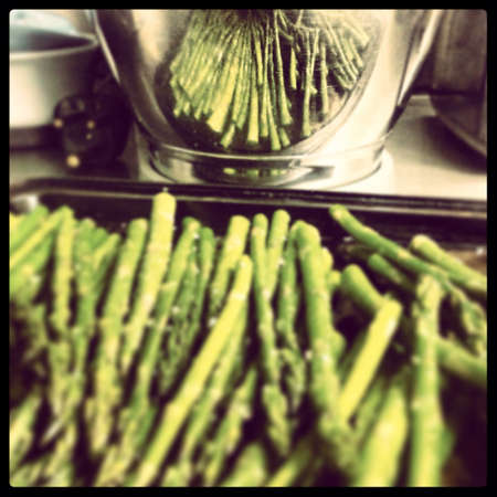 A tray of freshly grilled asparagus drizzled with olive oil and a hint of truffle oil