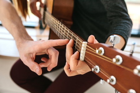 Photo pour Learning to play the guitar. Music education. - image libre de droit