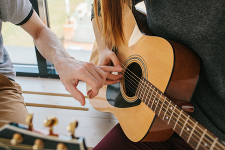 Photo pour Learning to play the guitar. Music education and extracurricular lessons. - image libre de droit
