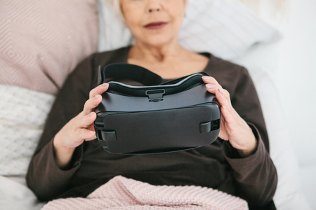 An elderly woman is going to put on virtual reality glasses to use them to immerse in the virtual world. The older generation and new technologies.