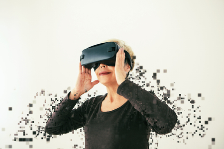An elderly woman in virtual reality glasses is scattered by pixels. Conceptual photography with visual effects with an elderly person using modern technology.