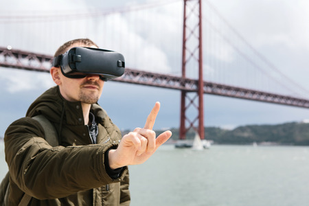 Foto de A man uses virtual reality glasses. 25th of April bridge in Lisbon in the background. The concept of virtual travel. The concept of modern technologies and their use in everyday life - Imagen libre de derechos