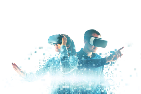 Foto de A young woman and a young man in virtual reality glasses are fragmented into pixels.The concept of modern technologies and technologies of the future. VR glasses. - Imagen libre de derechos