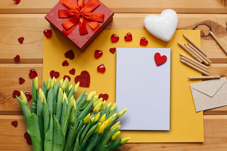 Foto de Blank sheet with red heart for text or write. Near an envelope to send and a box with a gift and a bouquet of yellow tulips. Concept for Valentines Day or Womens Day or Mothers Day. - Imagen libre de derechos