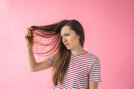 Photo pour The girl is not happy with her hair and shows split ends or dandruff or dry hair or other problems. - image libre de droit