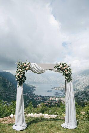 Foto de Beautiful wedding arch with flowers on the background of the Boko-Kotor Bay in Montenegro. Preparation for a wedding event. - Imagen libre de derechos
