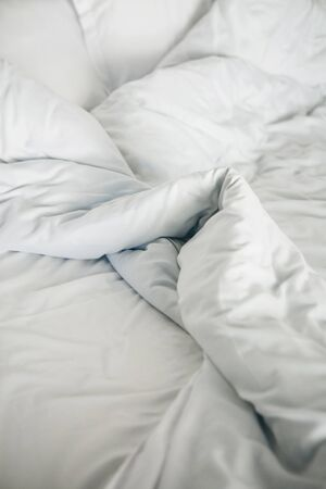 Photo pour Crumpled white blanket on the bed after sleeping in the morning - image libre de droit