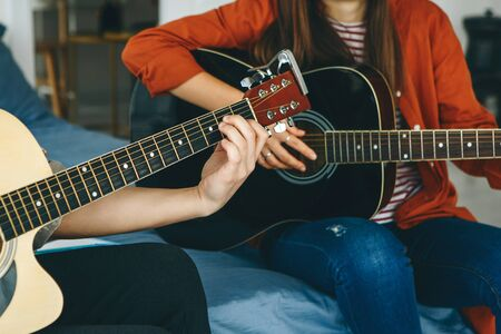 Photo pour Learning to play the guitar. The teacher explains to the student the basics of playing the guitar. Individual home schooling or extracurricular lessons. - image libre de droit