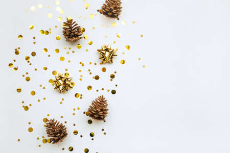 Photo pour Festive golden bows and cones on a white background with confetti. Christmas or New Year background. Nearby copy space or space for text. - image libre de droit
