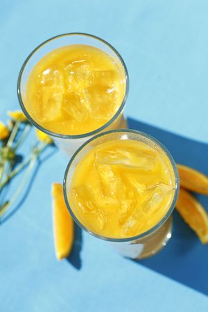 Two glasses of freshly squeezed orange juice with icecubes