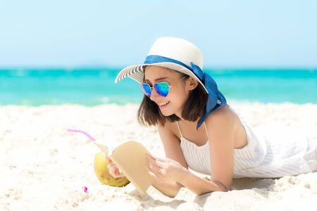Photo pour Lifestyle young  woman relax on the summer beach.  Asia tourism people reading and chill in holiday. blue sky background.  Summer Vacations Concept. - image libre de droit