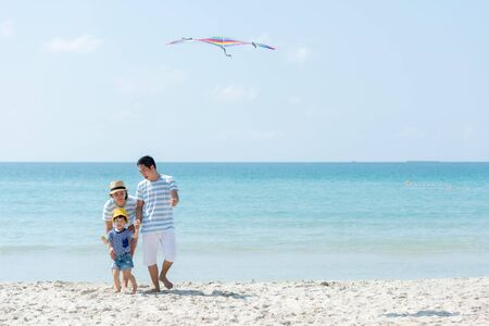 Photo for Happy family summer sea beach vacation. Asia youngpeople lifestyle travel play kite enjoy fun and relax in holiday. Travel and Family Concept - Royalty Free Image