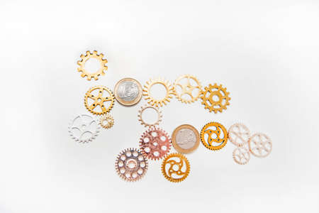 Photo pour Clock gear wheels on white table with euro coins. Money currency abstract photo. - image libre de droit