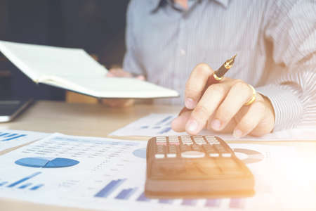 Foto de Business man or accountant working Financial investment on calculator with calculate Analyze business and market growth on financial document data graph and writing ,Accounting,Economic,commercial. - Imagen libre de derechos