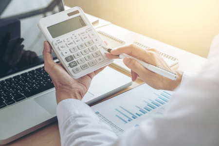 Photo pour Female accountant calculations and analyzing financial graph data with calculator and laptop Business, Financing, Accounting, Doing finance, Economy, Savings Banking Concept. - image libre de droit