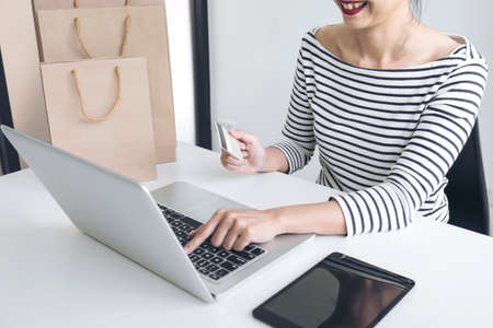 Woman\'s hands using credit card register and payments online shopping and customer service network connection market, using technology on laptop, Internet Online shopping or internet banking concept.