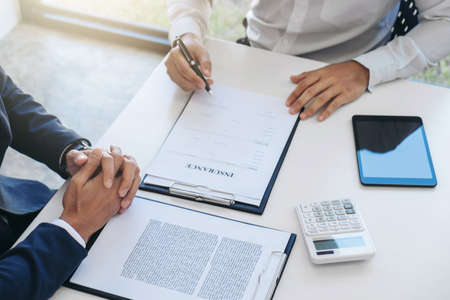 Photo pour Businessman will be signing a car insurance policy, Agent man is holding the document and waiting for his reply to finish. - image libre de droit