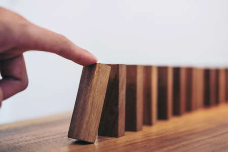 Photo pour Risk and strategy in business, Close up of businessman hand gambling starting push wooden block on a line of domino. - image libre de droit