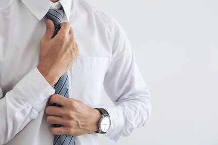 Photo pour Close up of Young attractive businessman wears a gray tie and adjusting tie. - image libre de droit